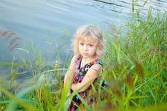 单独女孩一点河沿害怕的走 免版税库存照片