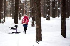 单独女孩在冬天森林里 免版税库存图片