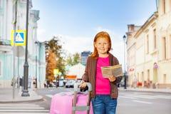 单独女孩立场在有城市地图的街道上 免版税库存照片