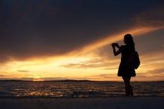 单独妇女剪影水边缘的,享受美好的海景在日落 免版税库存照片