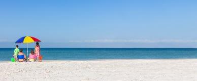 单独家庭在与伞的海滩 图库摄影