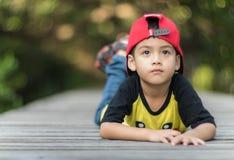 单独小男孩和奇迹盖帽呆在一起 免版税库存照片