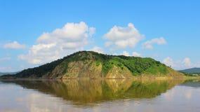 单独岩石海岛在与干净的反射和蓝色的寂静的水中 库存照片