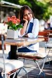 单独年轻美丽的亚裔妇女画象等待的咖啡馆的和天作梦 库存图片