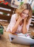 单独微笑的少妇有膝上型计算机的 库存图片