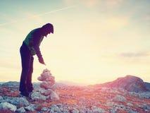 单独成人人库存石头对金字塔 阿尔卑斯山山顶,平衡太阳在天际 库存照片