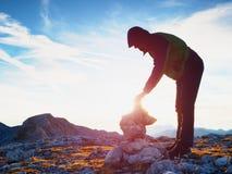 单独成人人库存石头对金字塔 阿尔卑斯山山顶,平衡太阳在天际 免版税库存照片