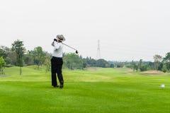 单独打高尔夫球在一个绿色高尔夫球场的老人 免版税库存照片