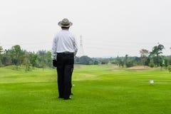 单独打高尔夫球在一个绿色高尔夫球场的老人 免版税库存图片