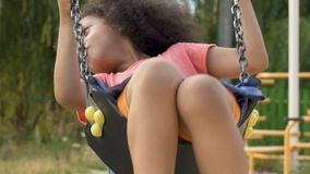 单独摇摆在孤儿院操场,关于家庭的梦想的小两种人种的女孩 股票录像