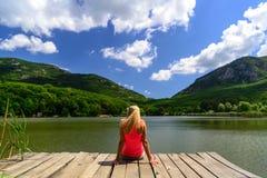 单独放松的妇女 湖和山晴朗的风景 库存图片