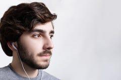单独放松年轻有胡子的时髦的人特写镜头户内,听在作梦关于某事的耳机的音乐轨道 免版税库存图片