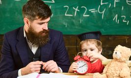 单独教育概念 老师和学生在教室 学会时间的小男孩 在毕业的逗人喜爱的孩子 免版税图库摄影