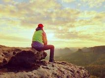 单独旅游采取绿色黑夹克的休息远足者坐岩石峰顶 免版税库存图片