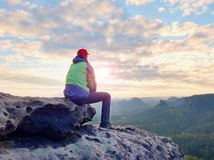 单独旅游采取绿色黑夹克的休息远足者坐岩石峰顶 库存照片