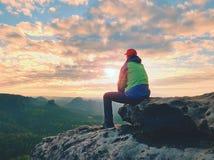 单独旅游采取绿色黑夹克的休息远足者坐岩石峰顶 库存图片