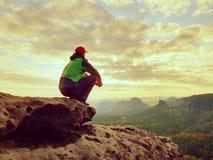 单独旅游采取绿色黑夹克的休息远足者坐岩石峰顶 免版税库存照片