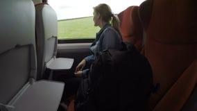 单独旅行在火车的沉思十几岁的女孩放松和看通过享受乡下风景的窗口- 股票视频