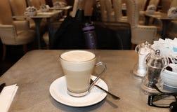 单独旅行-杯子在一张桌上的拿铁在有背包和水瓶的一个机场在椅子 免版税库存图片