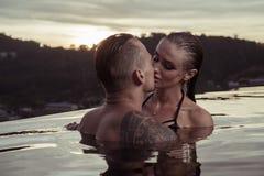 单独浪漫夫妇在无限游泳池 库存图片