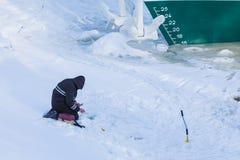 单独渔夫坐冬天河的冰和雪船的背景的 库存照片