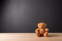 单独玩具熊玩具在木头在前面灰色背景中 库存图片