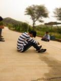 单独男孩坐路 免版税库存图片