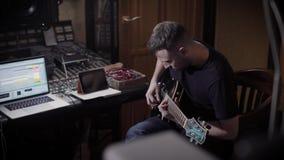单独男性吉他弹奏者在录音室弹吉他,坐在控制室 股票视频