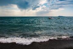 单独白色小的小船在有风暴天气的海 免版税库存照片