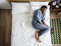 单独睡觉在床上的黑人 免版税库存照片
