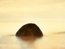 单独石头在光滑的海 与低lightt的美好的海景 构成本质岩石海运日落 库存照片