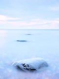 单独石头在光滑的海 与低lightt的美好的海景 构成本质岩石海运日落 库存图片