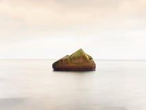 单独石头在光滑的海 与低lightt的美好的海景 构成本质岩石海运日落 免版税库存照片