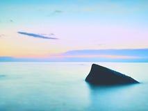 单独石头在光滑的海 与低lightt的美好的海景 构成本质岩石海运日落 免版税库存图片