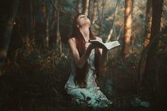 单独祈祷在森林里的妇女 免版税库存照片