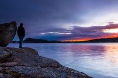 单独站立与他的Thoughs的一个人在五颜六色的Suset 免版税库存图片