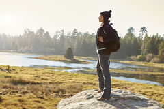 单独站立在一个岩石的年轻妇女在乡下 库存照片