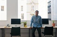 单独站立在一个现代办公室的年轻亚裔设计师 库存照片