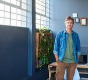 单独站立在一个现代办公室的微笑的年轻企业家 库存图片