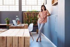 单独站立在一个现代办公室的微笑的年轻女实业家 图库摄影