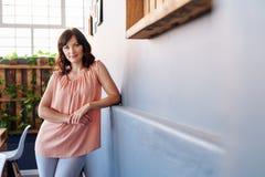 单独站立在一个现代办公室的微笑的年轻女性企业家 免版税库存图片