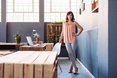 单独站立在一个现代办公室的确信的年轻女实业家 免版税库存照片
