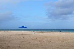 单独站立在一个白色沙子海滩的蓝色伞 库存照片