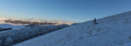 单独站立在与雪的小山的摄影师在日落, Sibil 库存图片