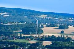 单独站立在小山的风车在导致电的德国 免版税库存照片