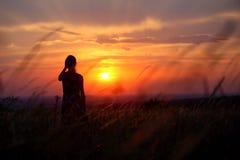 单独站立在日落期间的一个少妇的剪影 图库摄影