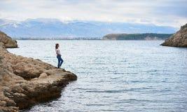 单独站立在海石岸的牛仔裤和T恤杉的年轻可爱的亭亭玉立的妇女  免版税库存图片