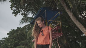 单独站立在海滩和看日落的年轻白肤金发的妇女 股票录像
