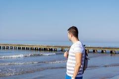 单独站立在海滩的年轻哀伤的人 免版税库存照片