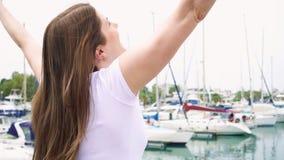 单独站立在码头的少妇 举她的胳膊在慢动作的被启发的无忧无虑的女性 股票录像